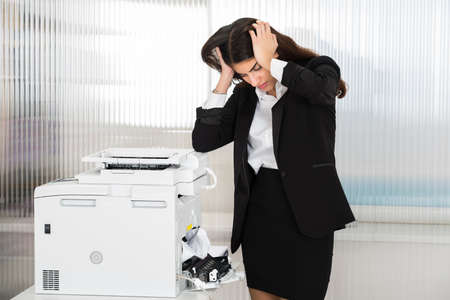 Irritated young businesswoman looking at paper stuck in printer at office