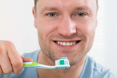 adult brushing teeth: Portrait of happy mid adult man brushing teeth against white background