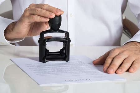 Midsection van zakenman stampen contract document bij bureau