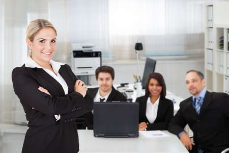 Portrait of young businesswoman standing arms crossed while colleagues sitting at desk in office photo