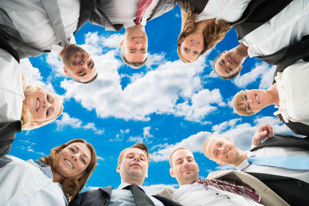 directly below: Directly below portrait of diverse business people forming huddle against sky