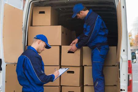Człowiek dostawy rozładunku kartonów z ciężarówki podczas pisania kolega w schowku