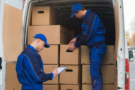 unloading: Delivery man unloading cardboard boxes from truck while colleague writing on clipboard