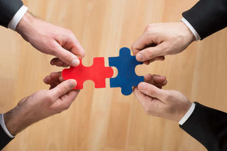 joining hands: Cropped image of businessmen assembling jigsaw puzzle representing teamwork in office