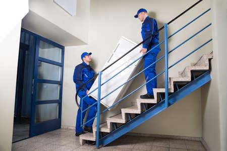 집에서 단계를 등반하는 동안 냉장고를 운반하는 발동기의 측면보기