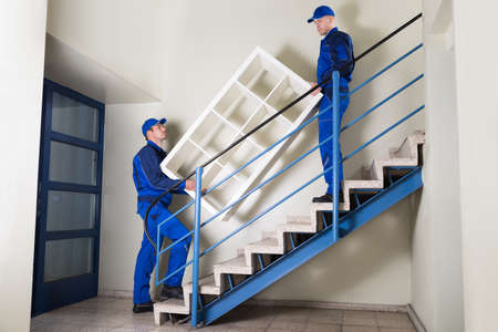 people moving: Full length of young movers carrying shelf while climbing steps at home Stock Photo