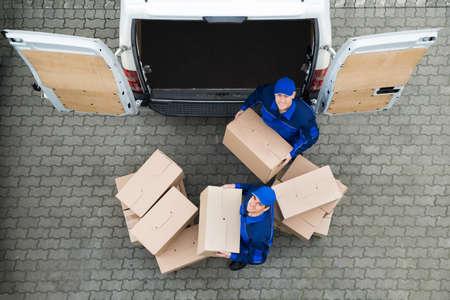 Directement au-dessus portrait de livraison des hommes portant des boîtes en carton à l'extérieur camion sur la rue