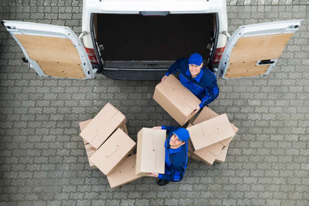 Directly above portrait of delivery men carrying cardboard boxes outside truck on street