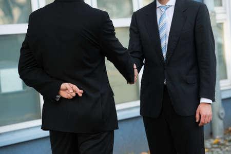 the finger: Sección media de hombre de negocios deshonesto con los dedos cruzados estrechar la mano con la pareja al aire libre