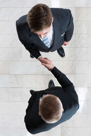 directly: Directly above shot of businessmen shaking hands while standing on tiled floor in office Stock Photo