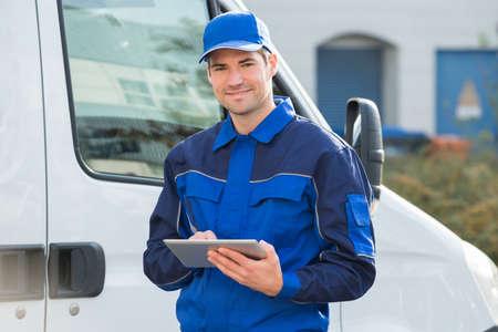 Portrait de livraison homme souriant à l'aide tablette numérique par camion