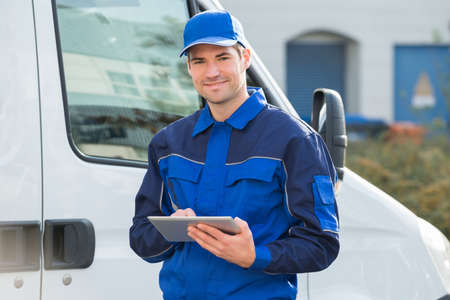delivery: Portrait of delivery man smiling using digital tablet by truck Stock Photo