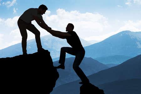 helping: Silueta del hombre joven que ayudar un amigo del varón en la escalada en roca Foto de archivo