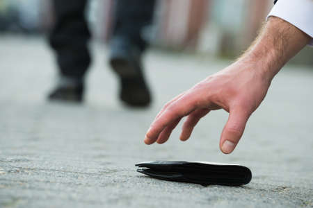 Cropped hand of businessman picking up fallen wallet on street