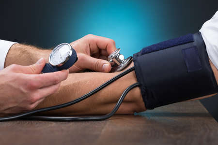 hipertension: Imagen recortada de médico de control de la presión arterial del paciente de sexo masculino en la mesa