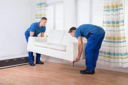 Longueur totale des déménageurs mâles placer un canapé sur le plancher de bois franc à la maison