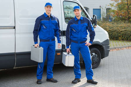 Full length portrait of confident technicians standing against truck on street Stockfoto