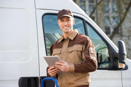Portret van lachende bezorging man die digitale tablet tegen vrachtwagen houdt
