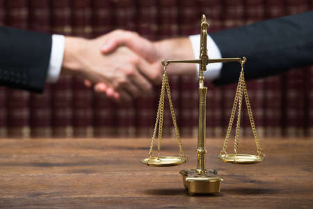 authority: Justice scale on wooden table with judge and client shaking hands in background at courtroom