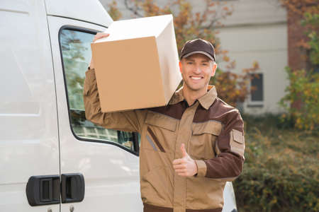 shoulder carrying: Portrait of young delivery man carrying cardboard box on shoulder with truck in background
