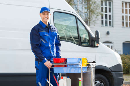 Portrait of happy male janitor standing with cleaning equipment against truck