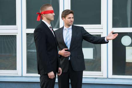 ojos vendados: Hombre de negocios joven confidente ayudar pareja fuera de la oficina con los ojos vendados Foto de archivo