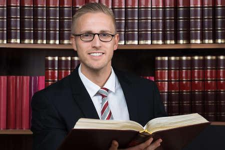 abogado: abogado de sexo masculino joven que lee el libro legal en la sala de audiencias Foto de archivo