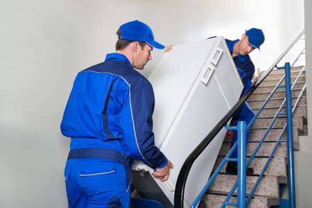 Young male movers carrying refrigerator while climbing steps at home