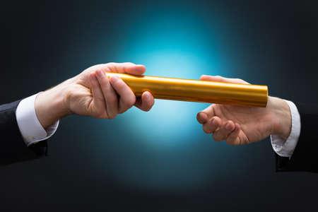 Bebouwde de hand van zakenman passeren gouden estafette stokje naar collega tegen een blauwe achtergrond