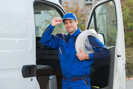 cable: Portrait of confident technician with cable coil and toolbox standing outside van Stock Photo