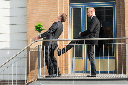 Side view of businessman kicking employee carrying box with belongings outside office