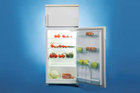 refrigerator with food: Open refrigerator full of healthy food isolated over blue background