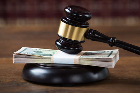 settlements: Closeup of mallet being hit on dollar bundle at table in courtroom