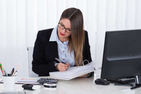 account executives: Young Businesswoman Calculating Tax At Office Desk