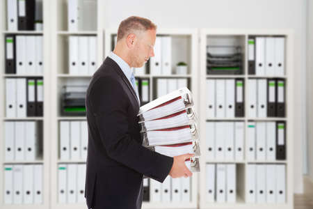 account executive: Side view of mid adult businessman carrying binders in office