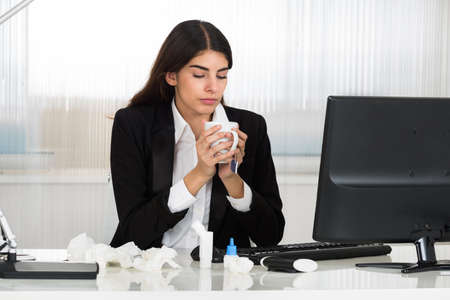 Sick young businesswoman holding cap of tee at computer desk in office