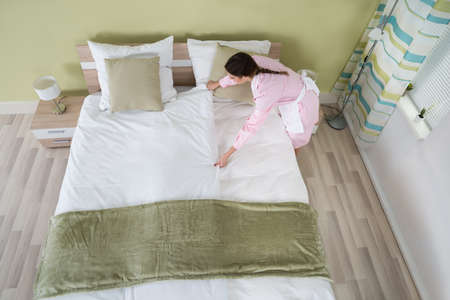 bedsheet: Young Female Housekeeper Arranging Bedsheet On Bed In Room Stock Photo