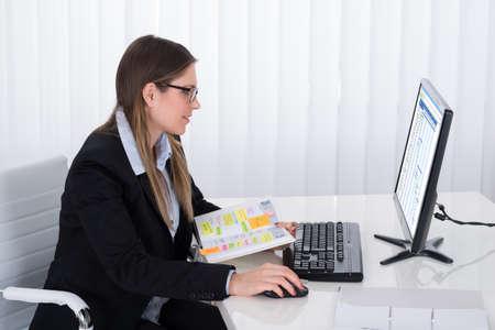 Empresaria joven con la lista de trabajo en diario que mira el ordenador