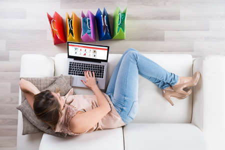 Young Woman On Sofa Shopping Online With Laptop