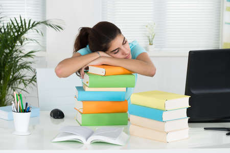 stacked books: Young female student resting on stacked books at table in home office Stock Photo