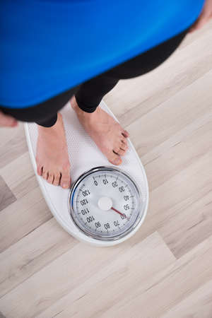 reduce: High Angle View Of Woman Measuring Body Weight On Weighing Scale