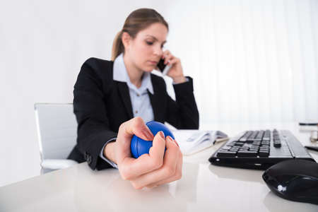 workplace wellness: Young Businesswoman Pressing Stressball While Talking On Mobile Phone At Desk