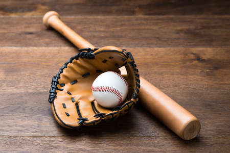 high angles: High angle view of baseball glove and ball with bat on wooden table