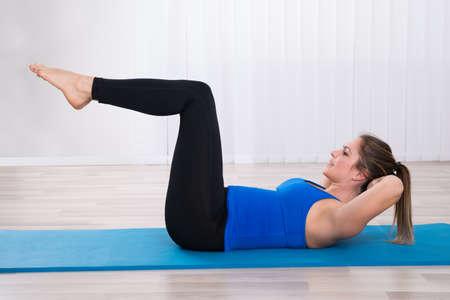 女性のヨガのクラス、体操用マットに鍛える