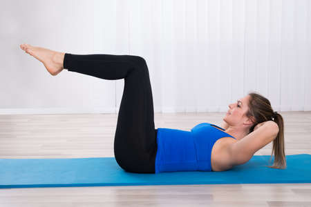 Woman Working Out On Exercise Mat In Yoga Class Stock Photo