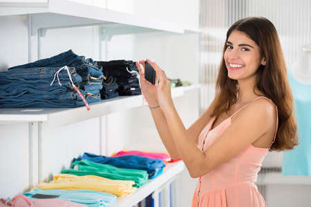 woman clothes: Portrait of happy young woman photographing garments through smartphone in retail store