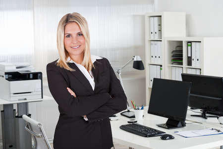 Portrait of young businesswoman standing arms crossed at desk in office photo