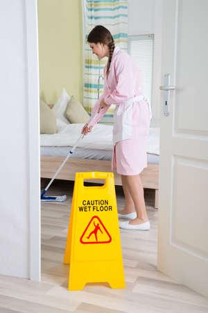 ama de llaves: Mujer joven ama de casa limpieza del piso con la fregona En La Habitaci�n