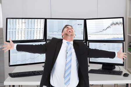arms trade: Happy stock broker laughing while standing with arms outstretched in office