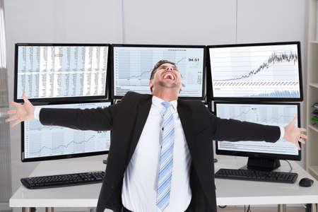 Heureux courtier en valeurs mobilières de rire en se tenant debout avec les bras tendus dans le bureau